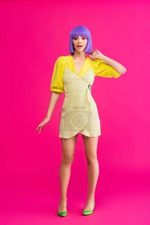 Photo pour Sexy attrayant pop art fille en perruque violette et robe jaune posant sur rose - image libre de droit