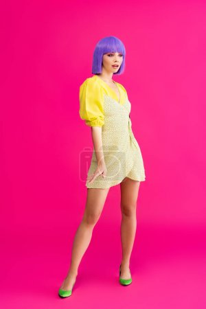 Photo pour Chic pop art girl in purple wig and yellow dress posing on pink - image libre de droit