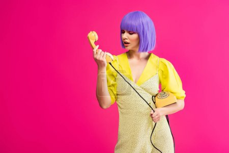 Photo for Emotional woman in purple wig holding retro telephone, isolated on pink - Royalty Free Image