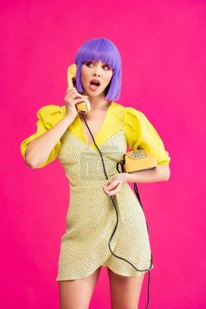 Photo pour Belle fille choquée en perruque violette parlant sur téléphone rétro, isolée sur rose - image libre de droit
