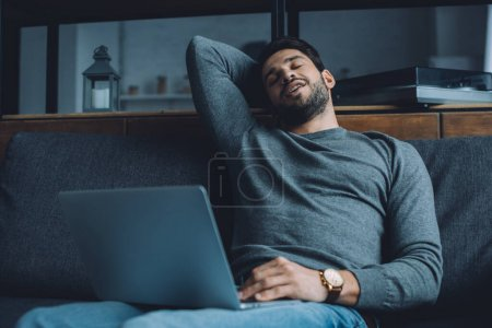 Photo pour Beau homme se masturber tout en regardant de la pornographie sur un ordinateur portable sur le canapé - image libre de droit