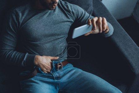 Photo pour Vue grand angle de jeune homme se masturber tout en regardant de la pornographie sur smartphone sur le canapé - image libre de droit