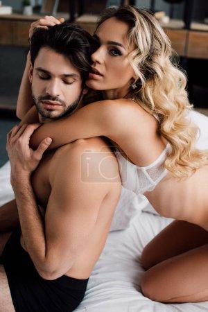 Photo pour Vue latérale de la femme sensuelle en soutien-gorge regardant la caméra et touchant les cheveux du petit ami musclé sur le lit - image libre de droit