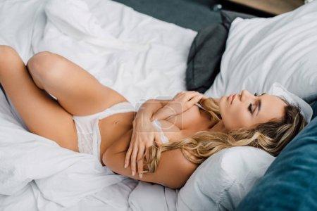 Photo pour Vue grand angle de la femme sensuelle en lingerie couchée sur le lit - image libre de droit
