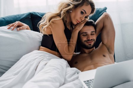 Attractive woman touching smiling man while looking at laptop on bed