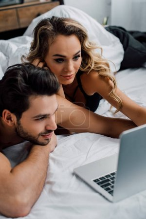 Photo for Handsome man looking at laptop near attractive girlfriend on bed - Royalty Free Image