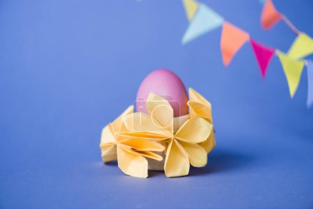 Photo for Selective focus of origami flowers near easter egg on blue - Royalty Free Image