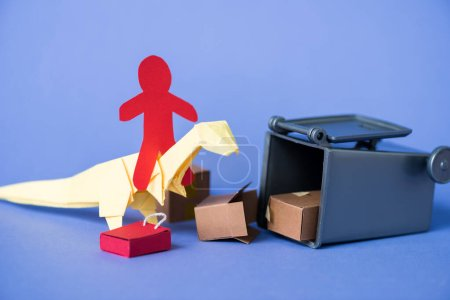 Photo for Paper human on origami dinosaur near trash can and carton boxes on blue - Royalty Free Image