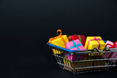 Photo for Selective focus of gift boxes in shopping basket isolated on black - Royalty Free Image