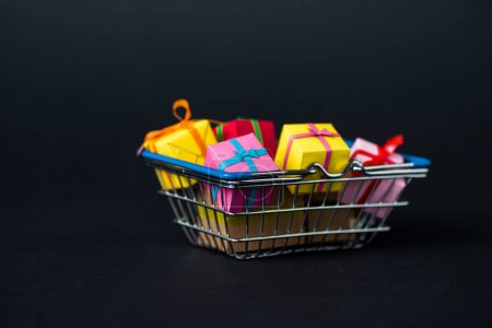 Photo for Selective focus of colorful gift boxes in shopping basket on black - Royalty Free Image