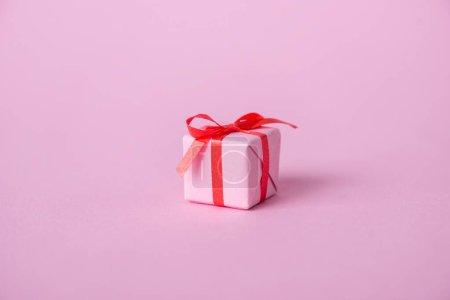 Photo pour Petit papier présent avec ruban et nœud sur rose - image libre de droit