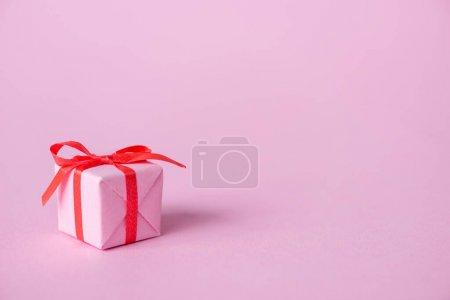 Photo pour Petit cadeau en papier avec ruban et noeud sur rose - image libre de droit