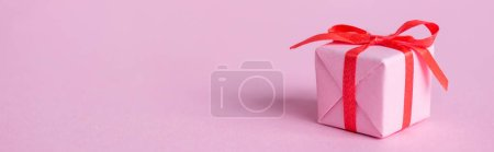 Photo for Panoramic shot of small paper gift with ribbon and bow on pink - Royalty Free Image