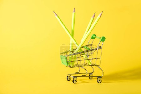 Photo for Toy shopping cart with pencils on yellow - Royalty Free Image