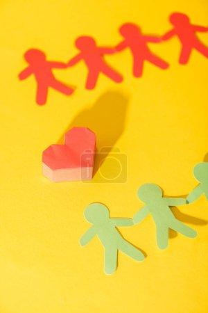 Foto de Corazón de origami cerca de gente de papel en amarillo - Imagen libre de derechos