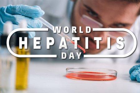Photo pour Foyer sélectif du scientifique tenant une pipette avec du liquide rouge en laboratoire avec illustration de la journée mondiale de l'hépatite - image libre de droit