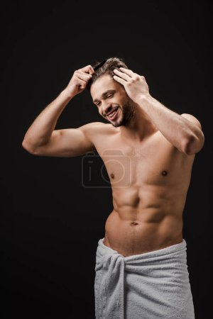 cheerful handsome man in towel combing hair isolated on black