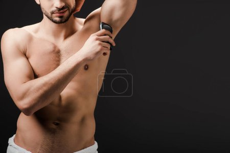 cropped view of sexy man applying deodorant on armpit isolated on black