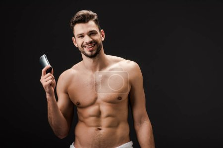 cheerful sexy man holding deodorant isolated on black
