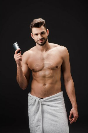 sexy smiling man holding deodorant isolated on black