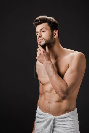 Photo for Pensive sexy man in towel touching beard isolated on black - Royalty Free Image