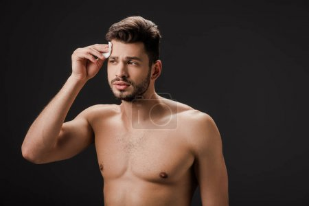 handsome sexy naked man using cosmetic cotton pad isolated on black