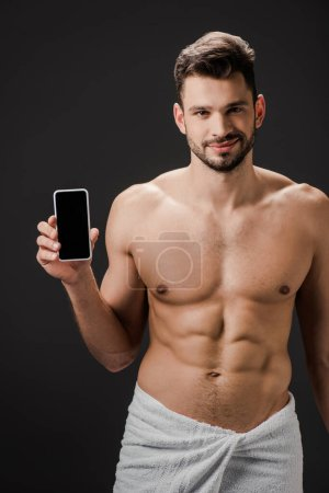 Photo for Smiling sexy man in towel showing smartphone with blank screen isolated on black - Royalty Free Image