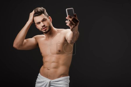 Photo for Sexy man in towel taking selfie on smartphone isolated on black - Royalty Free Image
