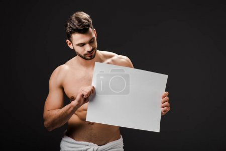 Photo for Sexy shirtless man in towel holding blank placard isolated on black - Royalty Free Image
