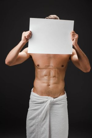 sexy shirtless man in towel holding blank placard in front of face isolated on black