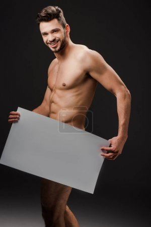 smiling sexy naked man holding blank placard isolated on black