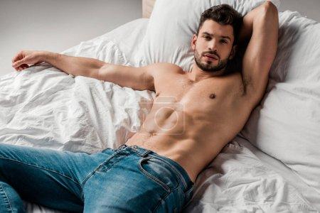 Photo pour Bel homme sexy torse nu en jeans couché sur le lit sur gris - image libre de droit