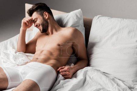 Photo pour Riant beau homme sexy couché sur le lit sur gris - image libre de droit