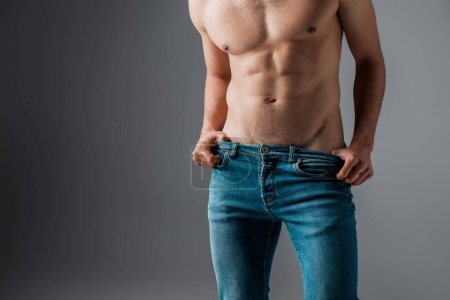 Photo for Cropped view of sexy muscular man in jeans on grey - Royalty Free Image