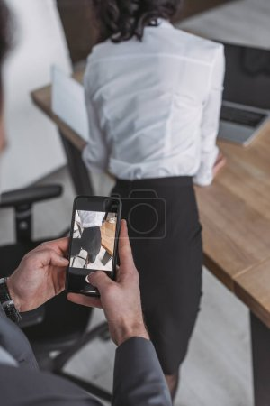 Photo for Cropped view of businessman taking photo of buttocks of secretary on smartphone - Royalty Free Image