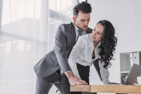 handsome businessman molesting displeased secretary in office