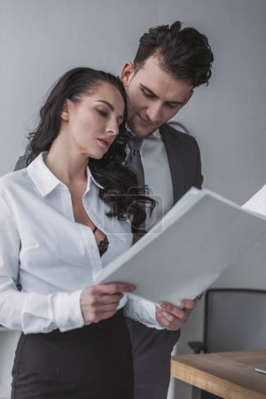 Photo for Sexy secretary showing papers to handsome businessman - Royalty Free Image
