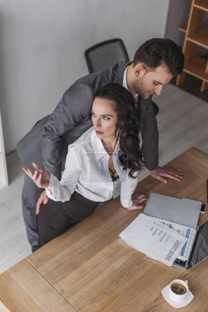 Photo for High angle view of businessman touching buttocks of angry secretary standing at workplace - Royalty Free Image