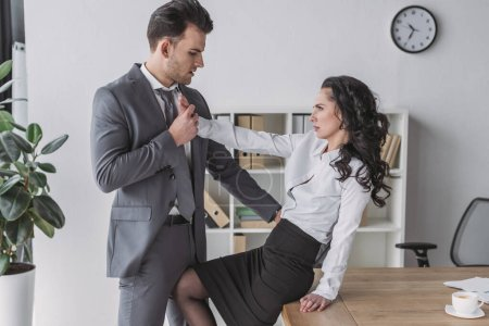 Photo for Angry secretary sitting on desk and pushing away businessman molesting her in office - Royalty Free Image