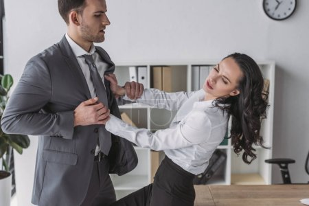 Photo for Displeased secretary pushing away businessman molesting her in office - Royalty Free Image