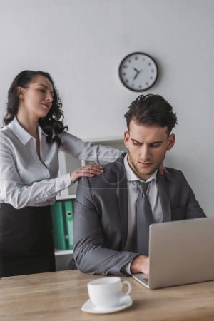 Photo for Sexy secretary touching shoulders of serious businessman working on laptop - Royalty Free Image