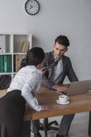 Photo pour Secrétaire sensuelle touchant cravate de beau homme d'affaires tout en le séduisant dans le bureau - image libre de droit