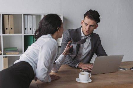 Photo pour Sexy secrétaire toucher cravate de beau homme d'affaires tout en le séduisant au bureau - image libre de droit