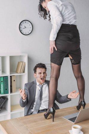 Photo pour Homme d'affaires en colère hurlant tout en regardant secrétaire sexy debout sur le bureau en chaussures à talons hauts - image libre de droit