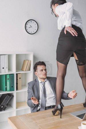 Photo pour Choqué homme d'affaires regardant secrétaire sexy debout sur le bureau en chaussures à talons hauts - image libre de droit
