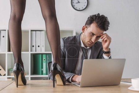 Photo pour Vue recadrée de secrétaire sexy en chaussures à talons hauts debout sur le bureau près de l'homme d'affaires travaillant sur ordinateur portable - image libre de droit