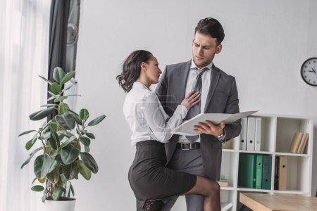 Photo pour Secrétaire sensuelle touchant homme d'affaires tout en le séduisant dans le bureau - image libre de droit