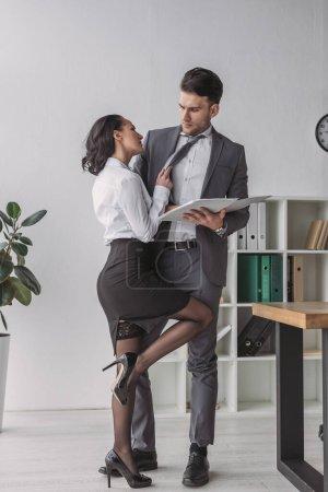 Photo pour Secrétaire sexy debout près de l'homme d'affaires tout en le séduisant dans le bureau - image libre de droit