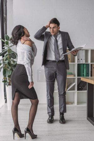 Photo for Seductive secretary touching her naked shoulder near shocked businessman - Royalty Free Image