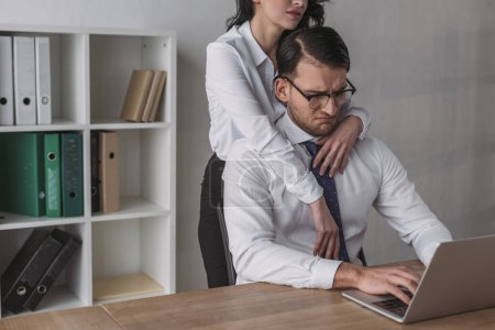 cropped view of sexy businesswoman embracing discouraged colleague working on laptop